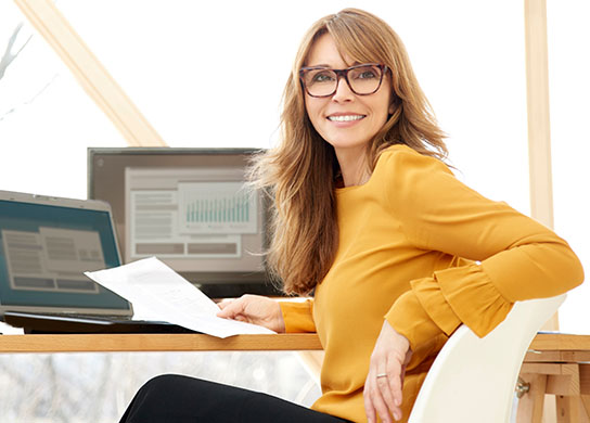 Woman working on computer, smiling while holding paperwork.