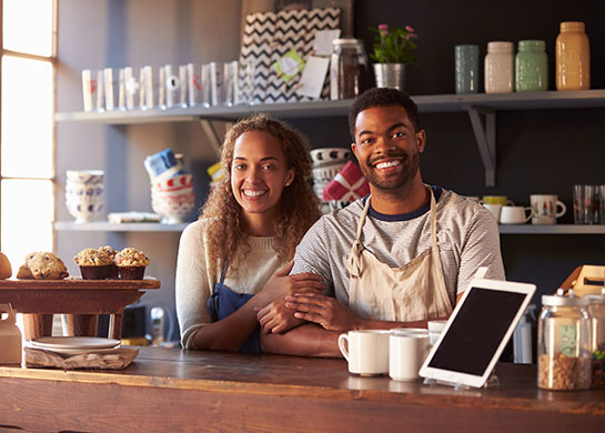 Small business owners smiling inside their open establishment.
