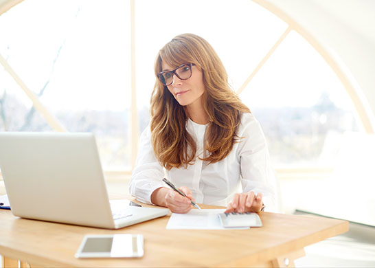 Professional woman filling out paperwork manually and on computer.
