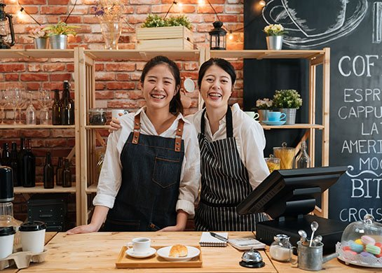 Small business owners smiling by the register of their coffee shop.