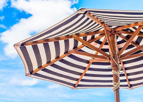 Striped patio umbrella against a blue sky.