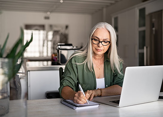 Woman working with notebook and laptop.