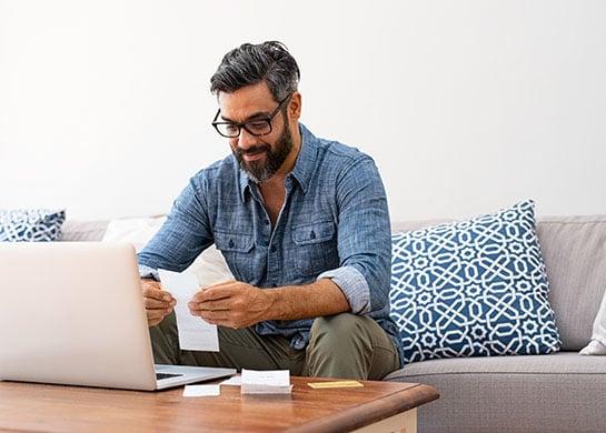 Man sitting at home paying bills online.