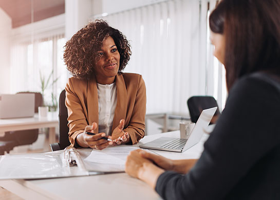 Professional woman working with client in an office setting.