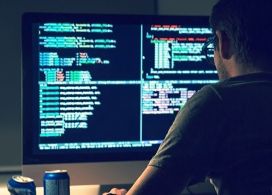 Back view of modern programmer sitting and writing code in dark room-655788-edited Featured Image